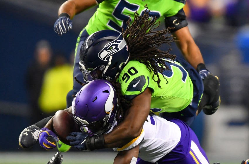 SEATTLE, WASHINGTON - DECEMBER 02: Jadeveon Clowney #90 of the Seattle Seahawks, top, knocks the ball loose from Dalvin Cook #33 of the Minnesota Vikings during the game at CenturyLink Field on December 02, 2019 in Seattle, Washington. The Seattle Seahawks won, 37-30. (Photo by Alika Jenner/Getty Images)
