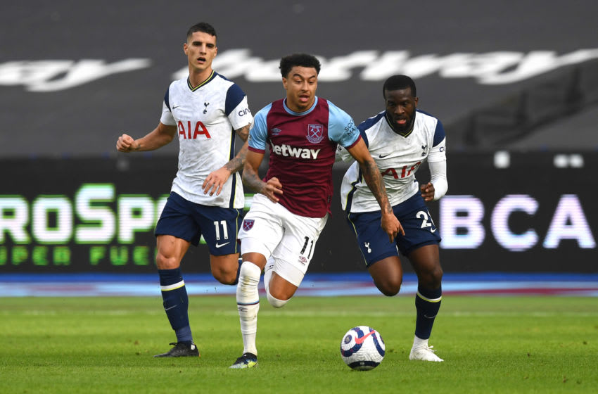 LONDON, ENGLAND - FEBRUARY 21: Jesse Lingard of West Ham United runs with the ball whilst under pressure from Tanguy Ndombele (R) and Erik Lamela of Tottenham Hotspur during the Premier League match between West Ham United and Tottenham Hotspur at London Stadium on February 21, 2021 in London, England. Sporting stadiums around the UK remain under strict restrictions due to the Coronavirus Pandemic as Government social distancing laws prohibit fans inside venues resulting in games being played behind closed doors. (Photo by Neil Hall - Pool/Getty Images)