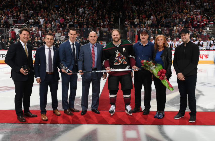 GLENDALE, ARIZONA - OCTOBER 19: Phil Kessel #81 of the Arizona Coyotes (C), along with father Phil Sr., mother Kathy and brother Blake, is presented with a silver stick celebrating his 1000th career NHL game by (from left) former Coyotes captain Shane Doan, team president Ahron Cohen, general manager John Chayka and Coyotes head coach Rick Tocchet during a ceremony prior to the start of a game against the Ottawa Senators at Gila River Arena on October 19, 2019 in Glendale, Arizona. (Photo by Norm Hall/NHLI via Getty Images)