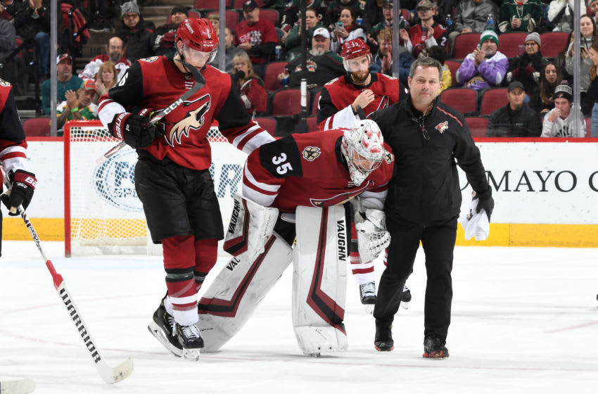 GLENDALE, ARIZONA - DECEMBER 19: Goalie Darcy Kuemper #35 of the Arizona Coyotes is assisted off the ice by teammate Jakob Chychrun #6 and Coyotes head athletic trainer Dave Zenobi after suffering an injury during the third period of the NHL hockey game against the Minnesota Wild at Gila River Arena on December 19, 2019 in Glendale, Arizona. (Photo by Norm Hall/NHLI via Getty Images)