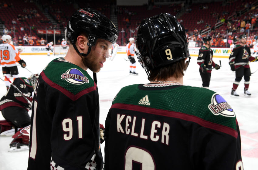 GLENDALE, ARIZONA - JANUARY 04: Taylor Hall #91 and Clayton Keller #9 of the Arizona Coyotes talk on the ice prior to the NHL hockey game against the Philadelphia Flyers at Gila River Arena on January 04, 2020 in Glendale, Arizona. (Photo by Norm Hall/NHLI via Getty Images)