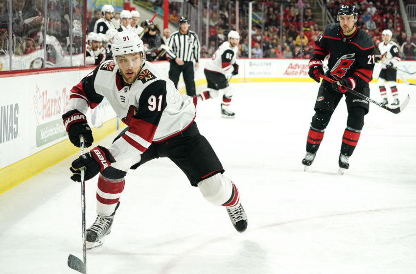 RALEIGH, NC - JANUARY 10: Arizona Coyotes Left Wing Taylor Hall (91) chases a puck into the boards during a game between the Arizona Coyotes and the Carolina Hurricanes on January 10, 2019 at the PNC Arena in Raleigh, NC. (Photo by Greg Thompson/Icon Sportswire via Getty Images)