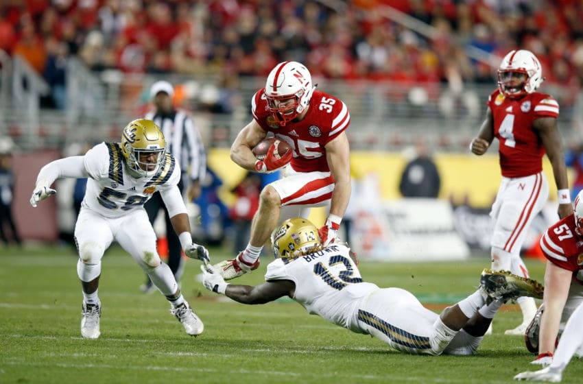 SANTA CLARA, CA - DECEMBER 26: Andy Janovich #35 of the Nebraska Cornhuskers jumps over Jayon Brown #12 of the UCLA Bruins during the Foster Farms Bowl at Levi's Stadium on December 26, 2015 in Santa Clara, California. (Photo by Ezra Shaw/Getty Images)