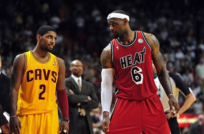 Feb 24, 2013; Miami, FL, USA; Cleveland Cavaliers point guard Kyrie Irving (left) looks over at Miami Heat small forward LeBron James (right) as Cleveland Cavaliers head coach Byron Scott (center) looks on during the second half at the American Airlines Arena. MIami won 109-105. Mandatory Credit: Steve Mitchell-USA TODAY Sports
