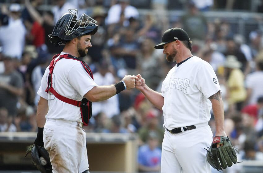 SAN DIEGO, CA - AUGUST 25: Kirby Yates #39 of the San Diego Padres, right, is congratulated by Austin Hedges #18 after defeating the Boston Red Sox 3-1 in a baseball game at Petco Park August 25, 2019 in San Diego, California. Teams are wearing special color schemed uniforms with players choosing nicknames to display for Players' Weekend. (Photo by Denis Poroy/Getty Images)