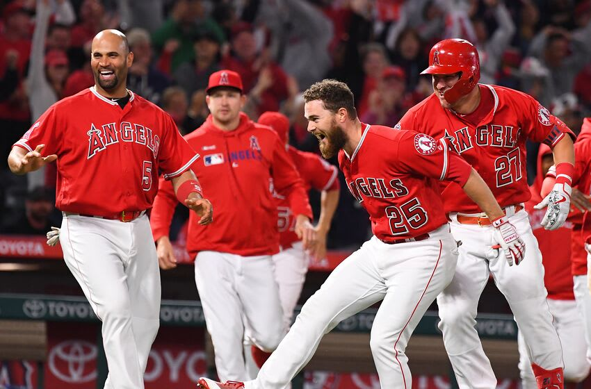 ANAHEIM, CA - MAY 25: Albert Pujols #5 and Mike Trout #27 celebrate with Jared Walsh #25 after he hit a walk off pinch hit single in the ninth inning of the game to score Kole Calhoun #56 of the Los Angeles Angels of Anaheim and defeat the Texas Rangers 3-2 at Angel Stadium of Anaheim on May 25, 2019 in Anaheim, California. (Photo by Jayne Kamin-Oncea/Getty Images)