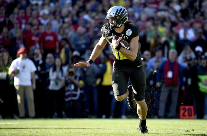 PASADENA, CALIFORNIA - JANUARY 01: Justin Herbert #10 of the Oregon Ducks runs the ball to score a four yard touchdown against the Wisconsin Badgers during the first quarter in the Rose Bowl game presented by Northwestern Mutual at Rose Bowl on January 01, 2020 in Pasadena, California. (Photo by Kevork Djansezian/Getty Images)