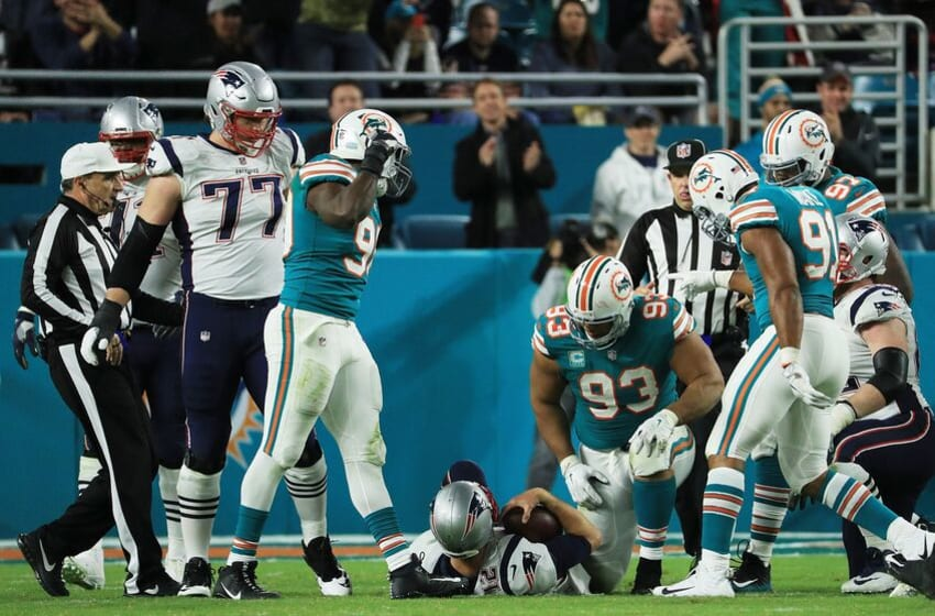 MIAMI GARDENS, FL - DECEMBER 11: Charles Harris #90 Cameron Wake #91 and Ndamukong Suh #93 of the Miami Dolphins celebrate sacking Tom Brady #12 of the New England Patriots in the fourth quarter at Hard Rock Stadium on December 11, 2017 in Miami Gardens, Florida. (Photo by Mike Ehrmann/Getty Images)