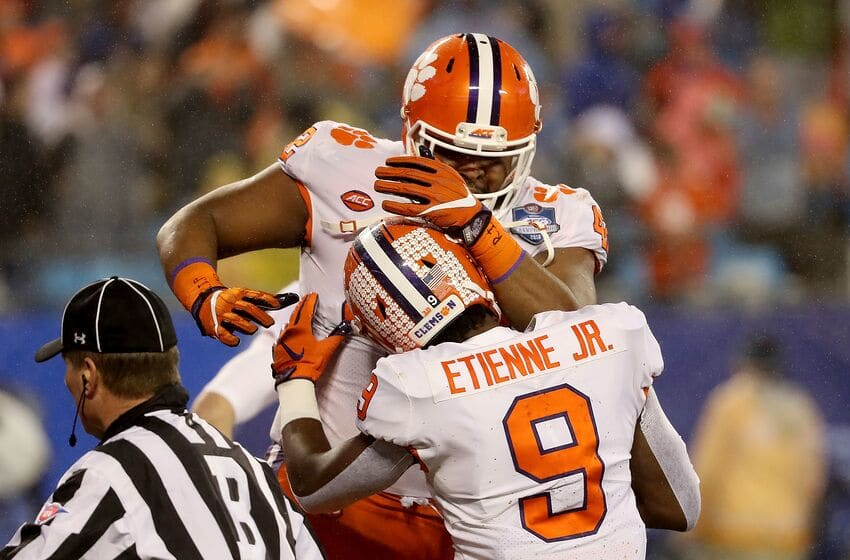 CHARLOTTE, NC - DECEMBER 01: Christian Wilkins #42 and teammate Travis Etienne #9 of the Clemson Tigers celebrate a touchdown against the Pittsburgh Panthers in the first quarter at Bank of America Stadium on December 1, 2018 in Charlotte, North Carolina. (Photo by Streeter Lecka/Getty Images)