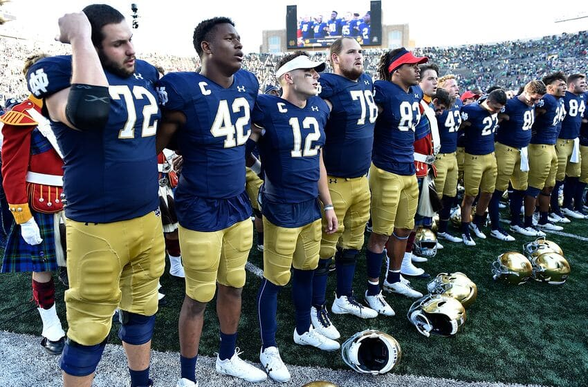 SOUTH BEND, INDIANA - SEPTEMBER 14: Ian Book #12, Julian Okwara #42, and teammates sing the alma mater after defeating the New Mexico Lobos at Notre Dame Stadium on September 14, 2019 in South Bend, Indiana. (Photo by Quinn Harris/Getty Images)