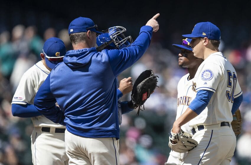 SEATTLE, WA - APRIL 28: Seattle Mariners manager Scott Servais (2L) signals to the bullpen as he pulls starting pitcher Erik Swanson #50 of the Seattle Mariners (R) during the fifth inning of a game against the Texas Rangers at T-Mobile Park on April 28, 2019 in Seattle, Washington. The Rangers won 14-1. (Photo by Stephen Brashear/Getty Images)