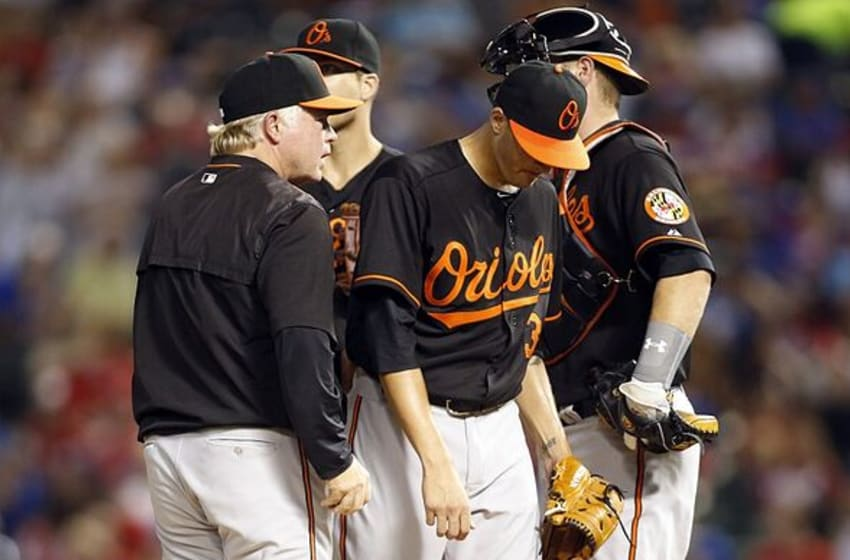 Aug 28, 2015; Arlington, TX, USA; Baltimore Orioles starting pitcher Kevin Gausman (39) leaves the mound after giving the ball to manager Buck Showalter (26) in the seventh inning against the Texas Rangers at Globe Life Park in Arlington. Texas won 4-1. Mandatory Credit: Tim Heitman-USA TODAY Sports