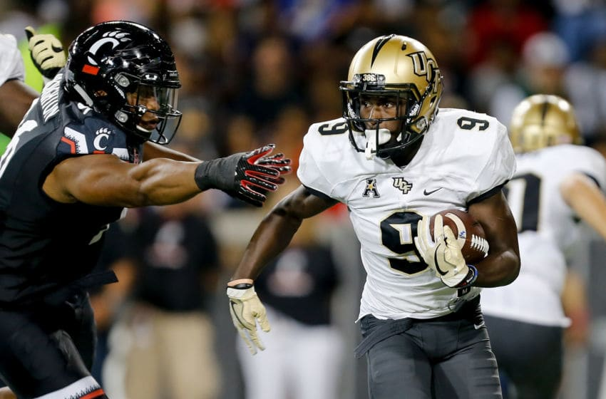 CINCINNATI, OH - OCTOBER 07: Adrian Killins Jr. #9 of the UCF Knights stiffs arms Cortez Broughton #96 of the Cincinnati Bearcats during the first half at Nippert Stadium on October 7, 2017 in Cincinnati, Ohio. (Photo by Michael Reaves/Getty Images)