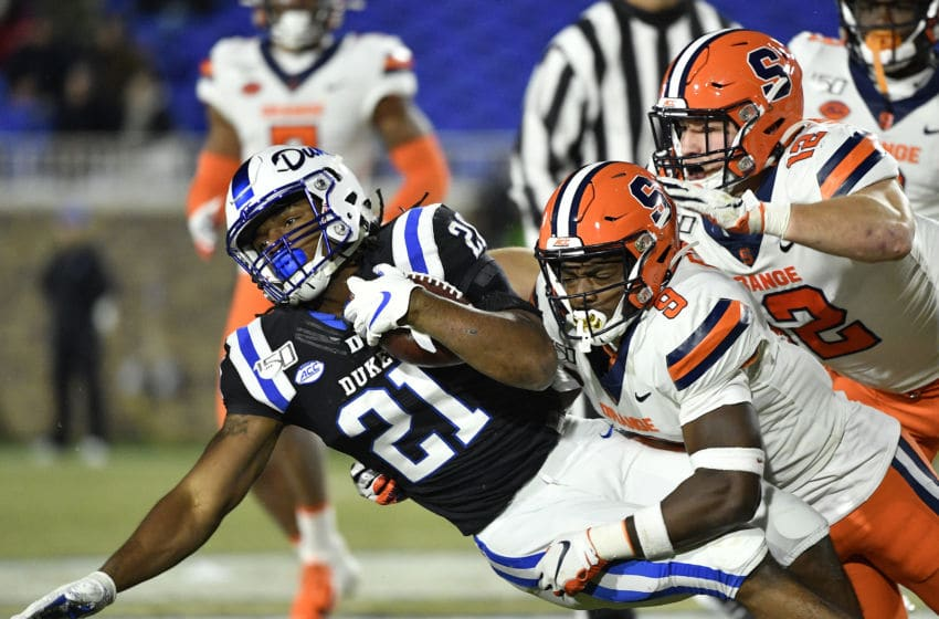 DURHAM, NORTH CAROLINA - NOVEMBER 16: Evan Foster #9 and Andrew Armstrong #12 of the Syracuse Orange tackle Mataeo Durant #21 of the Duke Blue Devils during the second half of their game at Wallace Wade Stadium on November 16, 2019 in Durham, North Carolina. (Photo by Grant Halverson/Getty Images)