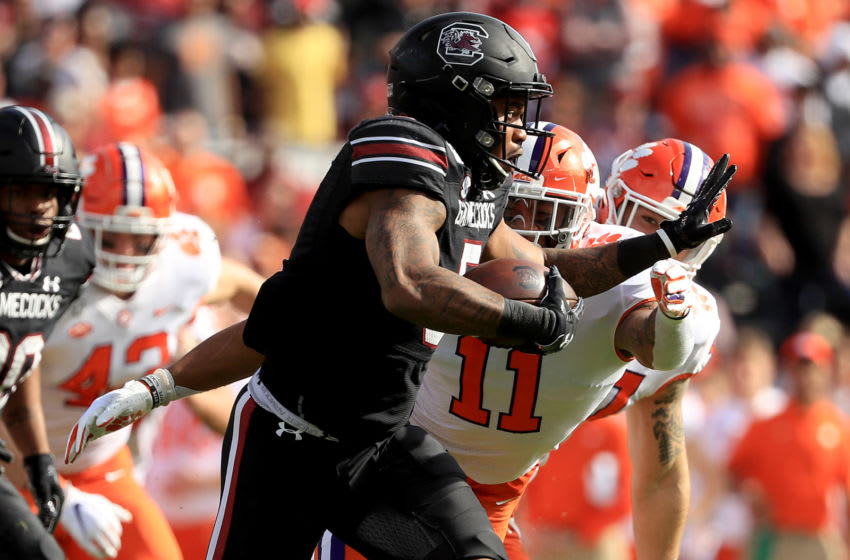COLUMBIA, SOUTH CAROLINA - NOVEMBER 30: Rico Dowdle #5 of the South Carolina Gamecocks runs with the ball against Isaiah Simmons #11 of the Clemson Tigers during their game at Williams-Brice Stadium on November 30, 2019 in Columbia, South Carolina. (Photo by Streeter Lecka/Getty Images)