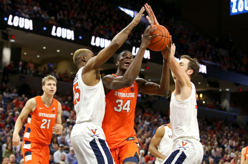 CHARLOTTESVILLE, VA - JANUARY 11: Bourama Sidibe #34 of the Syracuse Orange drives to the basket between Mamadi Diakite #25 and Jay Huff #30 of the Virginia Cavaliers in the first half during a game at John Paul Jones Arena on January 11, 2020 in Charlottesville, Virginia. (Photo by Ryan M. Kelly/Getty Images)