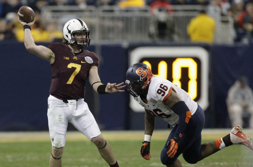 HOUSTON, TX - DECEMBER 27: Mitch Leidner #7 of the Minnesota Golden Gophers looks for a receiver as he is pressured by Jay Bromley #96 of the Syracuse Orange in the first half at Reliant Stadium on December 27, 2013 in Houston, Texas. (Photo by Bob Levey/Getty Images)