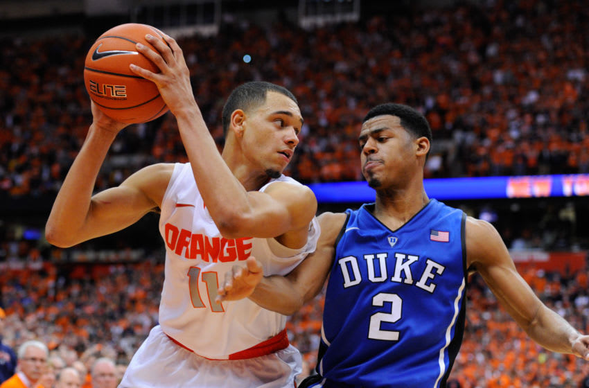 SYRACUSE, NY - FEBRUARY 01: Quinn Cook #2 of the Duke Blue Devils reaches to knock the ball out of the hands of Tyler Ennis #11 of the Syracuse Orange during overtime at the Carrier Dome on February 1, 2014 in Syracuse, New York. Syracuse defeated Duke 91-89 in overtime. (Photo by Rich Barnes/Getty Images)