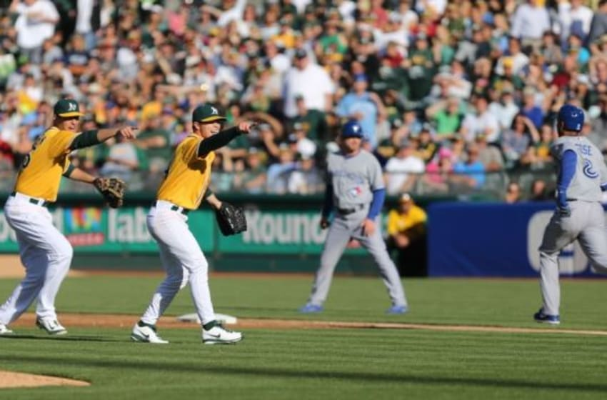 Jul 3, 2014; Oakland, CA, USA; Oakland Athletics first baseman Nate Freiman (35) and starting pitcher Sonny Gray (54) point to home for a play at the plate against the Toronto Blue Jays during the second inning at O.co Coliseum. Mandatory Credit: Kelley L Cox-USA TODAY Sports