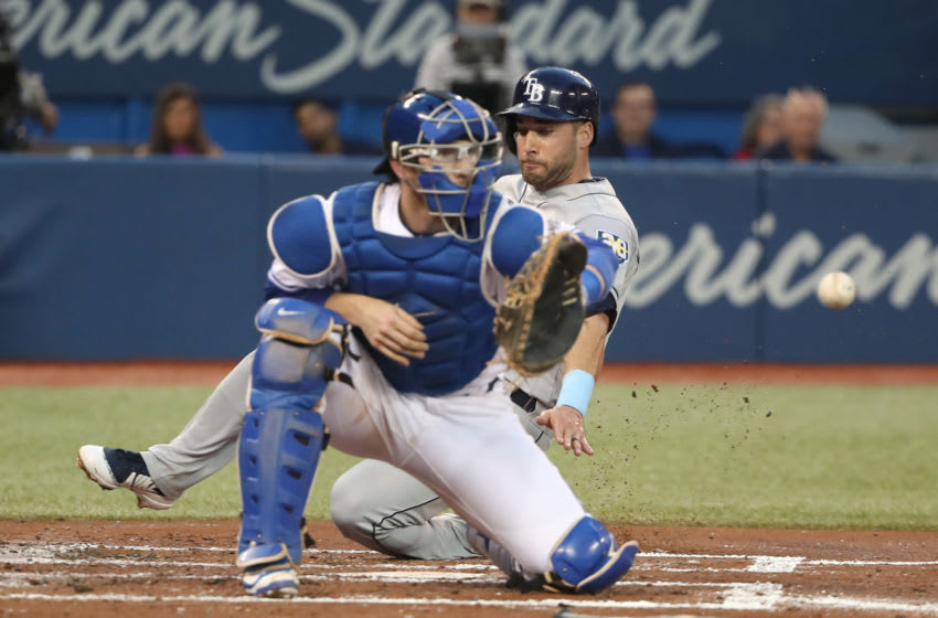 TORONTO, ON - SEPTEMBER 4: Kevin Kiermaier #39 of the Tampa Bay Rays slides across home plate to score a run on a fielders choice groundout in the second inning during MLB game action as Danny Jansen #9 of the Toronto Blue Jays waits for the throw at Rogers Centre on September 4, 2018 in Toronto, Canada. (Photo by Tom Szczerbowski/Getty Images)