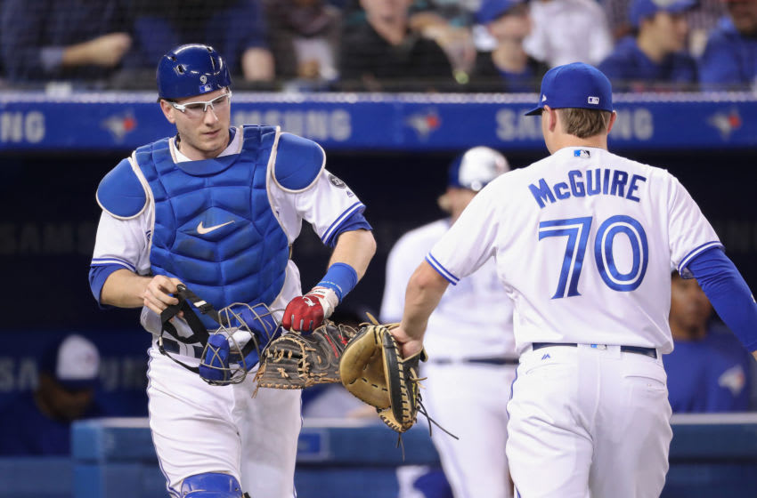 TORONTO, ON - SEPTEMBER 25: Danny Jansen #9 of the Toronto Blue Jays taps gloves with Reese McGuire #70 who helped him warm up the pitcher before the start of the next inning during MLB game action against the Houston Astros at Rogers Centre on September 25, 2018 in Toronto, Canada. (Photo by Tom Szczerbowski/Getty Images)