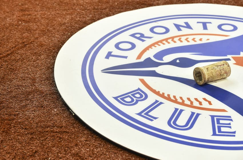 MONTREAL, QC - MARCH 26: A Toronto Blue Jays emblem is shown on the field against the Milwaukee Brewers during MLB spring training at Olympic Stadium on March 26, 2019 in Montreal, Quebec, Canada. The Toronto Blue Jays defeated the Milwaukee Brewers 2-0. (Photo by Minas Panagiotakis/Getty Images)