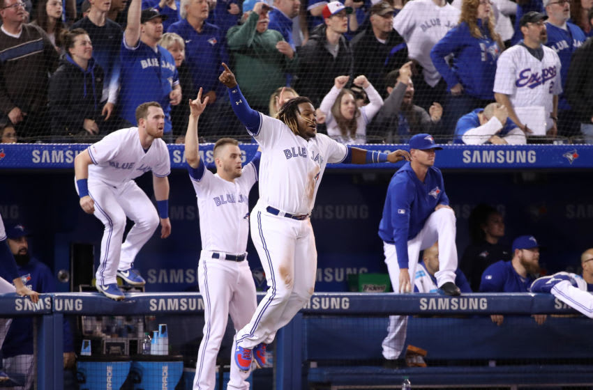 TORONTO, ON - APRIL 26: Vladimir Guerrero Jr. #27 of the Toronto Blue Jays celebrates their victory with Billy McKinney #28 and Ken Giles #51 as Brandon Drury #3 hit a game-winning two-run home run in the ninth inning during MLB game action against the Oakland Athletics at Rogers Centre on April 26, 2019 in Toronto, Canada. (Photo by Tom Szczerbowski/Getty Images)