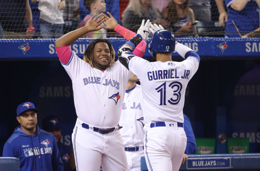 TORONTO, ON - MAY 26: Lourdes Gurriel Jr. #13 of the Toronto Blue Jays is congratulated by Vladimir Guerrero Jr. #27 after hitting a solo home run in the fourth inning during MLB game action against the San Diego Padres at Rogers Centre on May 26, 2019 in Toronto, Canada. (Photo by Tom Szczerbowski/Getty Images)