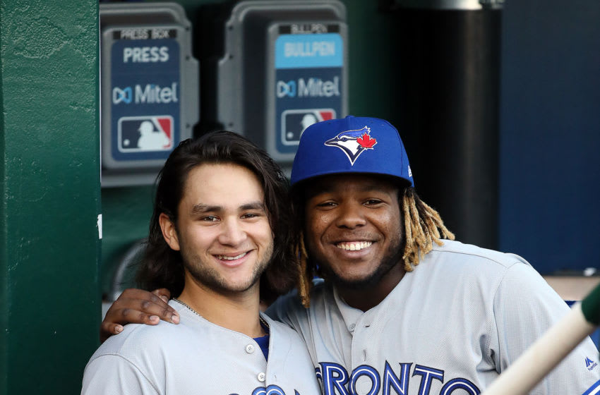 KANSAS CITY, MISSOURI - JULY 30: Shortstop Bo Bichette and third-baseman Vladimir Guerrero, Jr. #27 of the Toronto Blue Jays pose in the dugout prior to the game against the Kansas City Royals at Kauffman Stadium on July 30, 2019 in Kansas City, Missouri. (Photo by Jamie Squire/Getty Images)