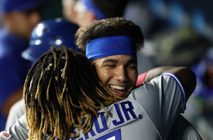 KANSAS CITY, MISSOURI - JULY 30: Vladimir Guerrero Jr. #27 of the Toronto Blue Jays is congratulated by Lourdes Gurriel Jr. #13 in the dugout after hitting a grand slam home run during the 9th inning of the game against the Kansas City Royals at Kauffman Stadium on July 30, 2019 in Kansas City, Missouri. (Photo by Jamie Squire/Getty Images)