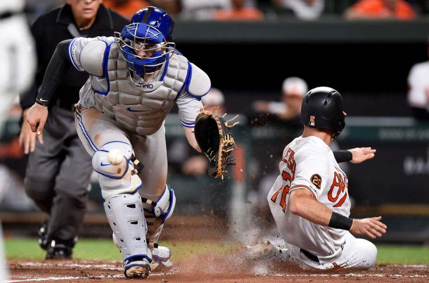 BALTIMORE, MD - SEPTEMBER 17: Stevie Wilkerson #12 of the Baltimore Orioles scores in the seventh inning ahead of the throw to Danny Jansen #9 of the Toronto Blue Jays at Oriole Park at Camden Yards on September 17, 2019 in Baltimore, Maryland. (Photo by Greg Fiume/Getty Images)