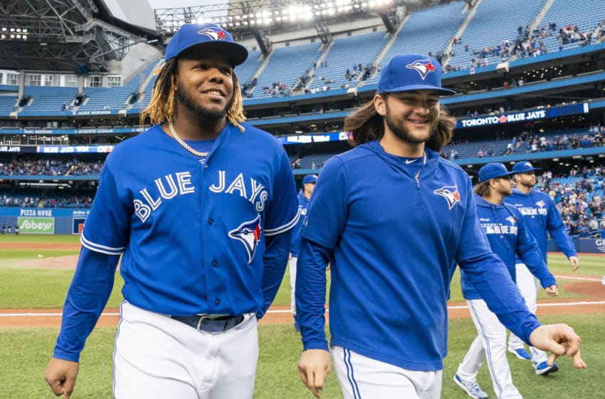 TORONTO, ONTARIO - SEPTEMBER 29: Vladimir Guerrero Jr. #27 and Bo Bichette #11 of the Toronto Blue Jays walk off the field after defeating the Tampa Bay Rays in the last game of the season in their MLB game at the Rogers Centre on September 29, 2019 in Toronto, Canada. (Photo by Mark Blinch/Getty Images)