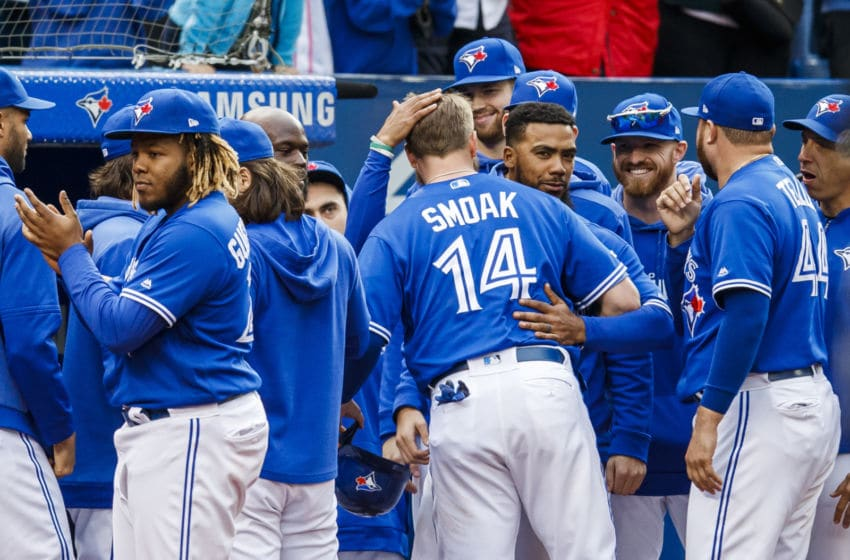 TORONTO, ONTARIO - SEPTEMBER 29: Justin Smoak #14 of the Toronto Blue Jays is congratulated by teammates Teoscar Hernandez #37 and Vladimir Guerrero Jr. #27 after hitting a double and being taken out of the game against the Tampa Bay Rays in the seventh inning during their MLB game at the Rogers Centre on September 29, 2019 in Toronto, Canada. (Photo by Mark Blinch/Getty Images)