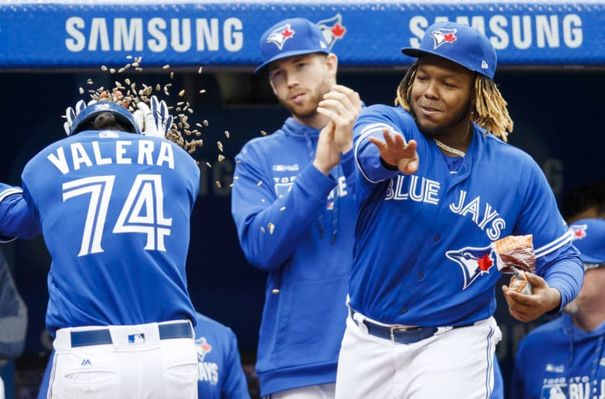 TORONTO, ONTARIO - SEPTEMBER 29: Breyvic Valera #74 of the Toronto Blue Jays is gets sunflower seeds thrown at him by teammate Vladimir Guerrero Jr. #27 after hitting a home run against the Tampa Bay Rays in the sixth inning during their MLB game at the Rogers Centre on September 29, 2019 in Toronto, Canada. (Photo by Mark Blinch/Getty Images)