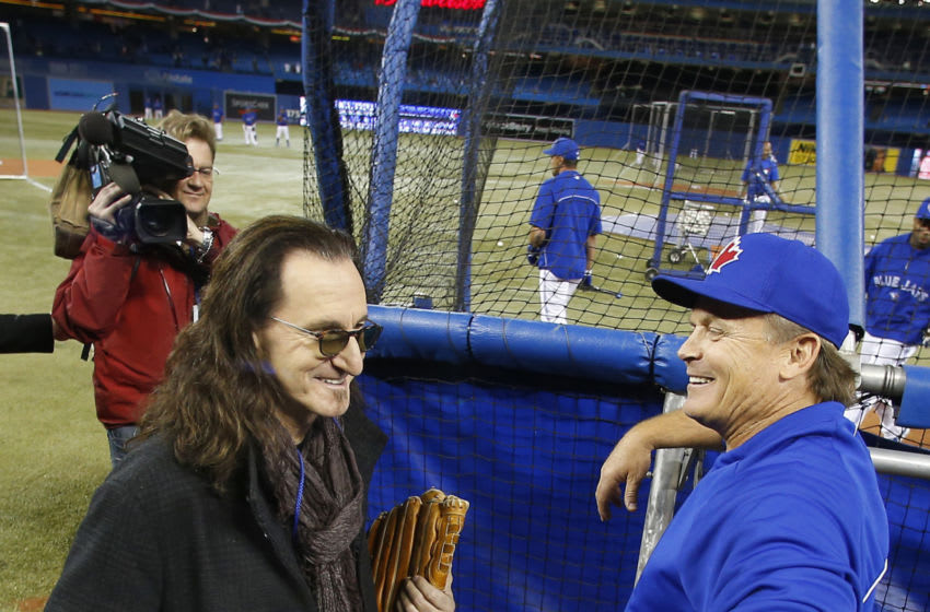TORONTO, CANADA - APRIL 02: Rush singer Geddy Lee talks to manager John Gibbons #52 of the Toronto Blue Jays during batting practice before the start of MLB game action on Opening Day against the Cleveland Indians on April 2, 2013 at Rogers Centre in Toronto, Ontario, Canada. (Photo by Tom Szczerbowski/Getty Images)