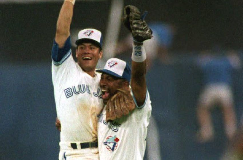 TORONTO, CANADA: Toronto Blue Jay Roberto Alomar (L) jumps into the arms of Joe Carter (R) after winning game six of the American League Championship Series against the Oakland A's at Toronto's Skydome 14 October, 1992. The Jays beat the A's 9-2 to advance to the World Series, the first time a Canadian team has been in the series. (Photo credit should read CHRIS WILKINS/AFP via Getty Images)