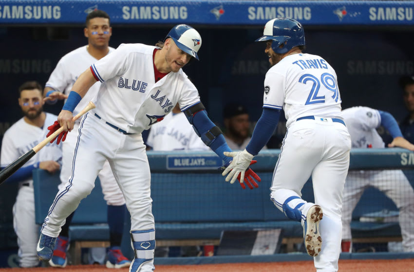 TORONTO, ON - MAY 23: Devon Travis #29 of the Toronto Blue Jays is congratulated by Josh Donaldson #20 after hitting a solo home run in the third inning during MLB game action against the Los Angeles Angels of Anaheim at Rogers Centre on May 23, 2018 in Toronto, Canada. (Photo by Tom Szczerbowski/Getty Images)