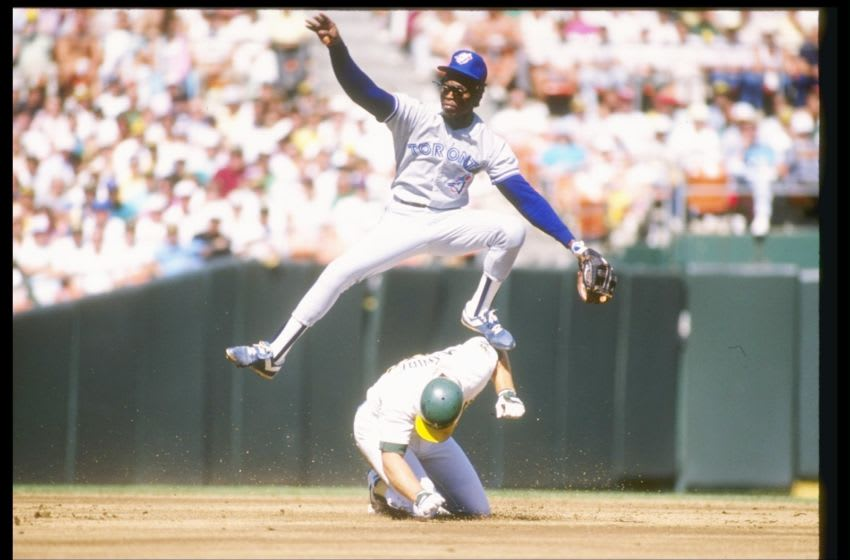 1989: Tony Fernandez of the Toronto Blue Jays leaps over first baseman Mark McGwire of the Oakland Athletics during a game of the 1989 American League Championship. Mandatory Credit: Otto Greule /Allsport