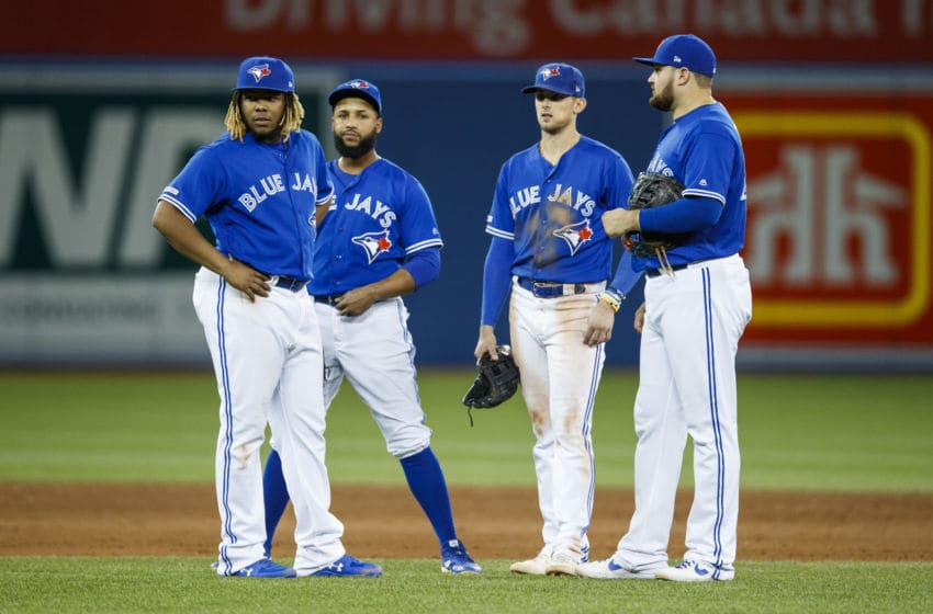TORONTO, ONTARIO - SEPTEMBER 27: Vladimir Guerrero Jr. #27, Richard Urena #7, Cavan Biggio #8, and Teoscar Hernandez #37 of the Toronto Blue Jays stand on the field in a break against the Tampa Bay Rays in the seventh inning during their MLB game at the Rogers Centre on September 27, 2019 in Toronto, Canada. (Photo by Mark Blinch/Getty Images)