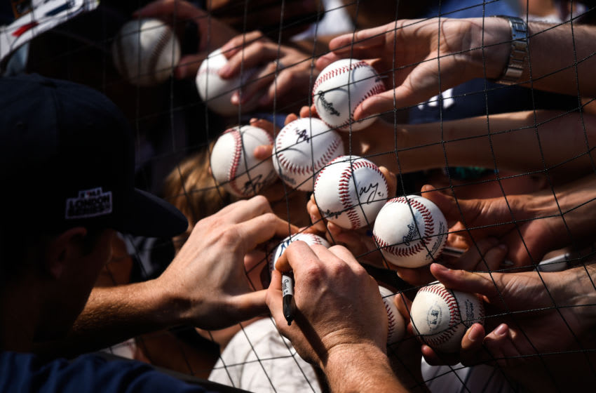 LONDON, ENGLAND - JUNE 28: Baseball fans hold out baseballs to be signed at The London Stadium on June 28, 2019 in London, England. The New York Yankees are playing the Boston Red Sox this weekend in the first Major League Baseball game to be held in Europe. (Photo by Peter Summers/Getty Images)
