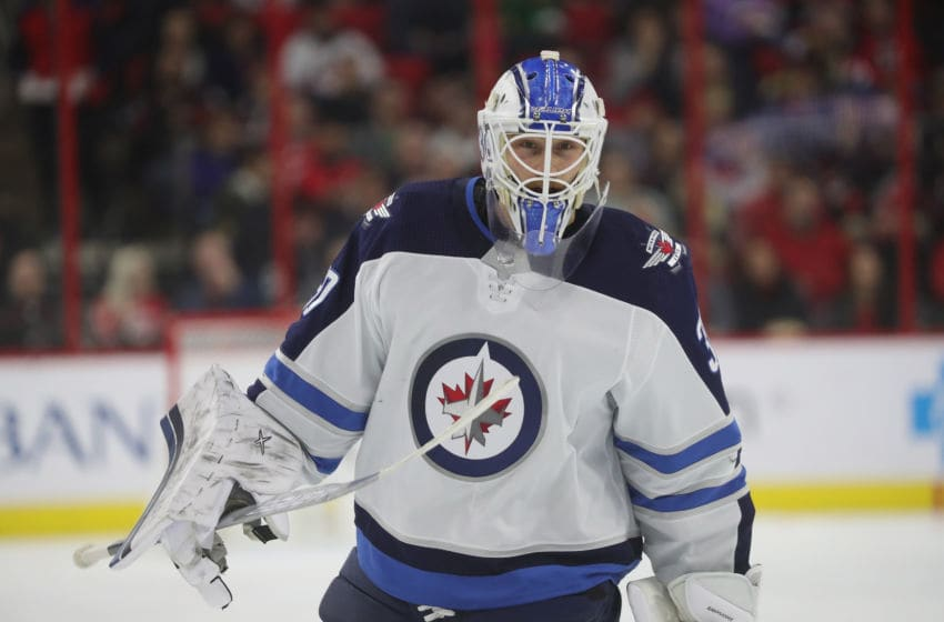 RALEIGH, NC - MARCH 08: Laurent Brossoit #30 of the Winnipeg Jets skates off the ice after the 1st period of play during an NHL game against the Carolina Hurricanes on March 8, 2019 at PNC Arena in Raleigh, North Carolina. (Photo by Gregg Forwerck/NHLI via Getty Images)