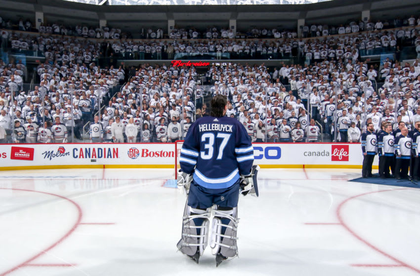 WINNIPEG, MB - APRIL 12: Goaltender Connor Hellebuyck #37 of the Winnipeg Jets stands on the ice during the singing of the National anthems prior to puck drop against the St. Louis Blues in Game Two of the Western Conference First Round during the 2019 NHL Stanley Cup Playoffs at the Bell MTS Place on April 12, 2019 in Winnipeg, Manitoba, Canada. (Photo by Jonathan Kozub/NHLI via Getty Images)