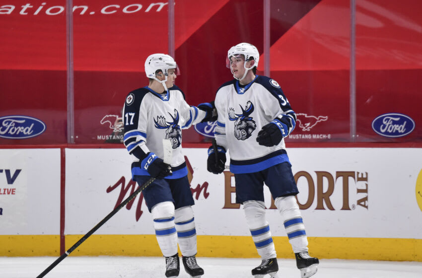 MONTREAL, QC - FEBRUARY 22: Ville Heinola #34 of the Manitoba Moose (R) celebrates his overtime goal with teammate Cole Perfetti #17 (L) against the Laval Rocket at the Bell Centre on February 22, 2021 in Montreal, Canada. The Manitoba Moose defeated the Laval Rocket 3-2 in overtime. (Photo by Minas Panagiotakis/Getty Images)