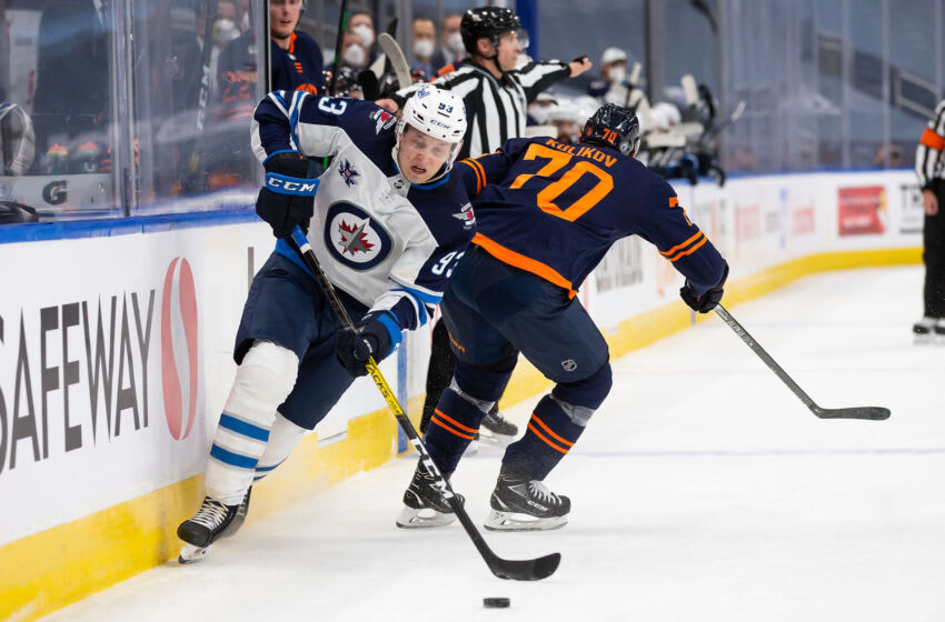 EDMONTON, AB - MAY 19: Kristian Vesalainen #93 of the Winnipeg Jets is hip checked by Dmitry Kulikov #70 of the Edmonton Oilers during Game One of the First Round of the 2021 Stanley Cup Playoffs at Rogers Place on May 19, 2021 in Edmonton, Canada. (Photo by Codie McLachlan/Getty Images)