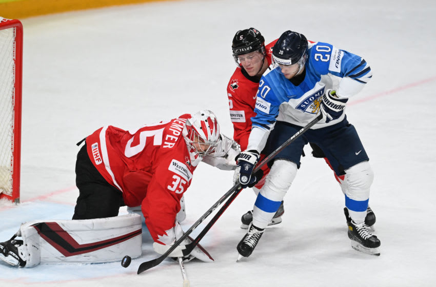 (L-R) Canada's goalkeeper Darcy Kuemper, Canada's defender Jacob Bernard-Docker and Finland's forward Niko Ojamaki vie for the puck during the IIHF Men's Ice Hockey World Championships preliminary round group B match between Canada and Finland, at the Arena Riga in Riga, on June 1, 2021. (Photo by Gints IVUSKANS / AFP) (Photo by GINTS IVUSKANS/AFP via Getty Images)