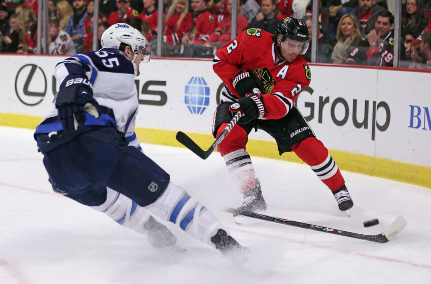 CHICAGO, IL - NOVEMBER 02: Duncan Keith #2 of the Chicago Blackhawks fires the puck past Mark Scheifele #55 of the Winnipeg Jets at the United Center on November 2, 2014 in Chicago, Illinois. (Photo by Jonathan Daniel/Getty Images)