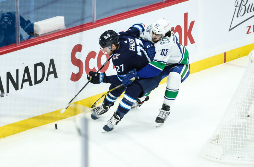 Jan 30, 2021; Winnipeg, Manitoba, CAN; Vancouver Canucks defenseman Jalen Chatfield (63) holds Winnipeg Jets forward Nikolaj Ehlers (27) during the third period at Bell MTS Place. Mandatory Credit: Terrence Lee-USA TODAY Sports