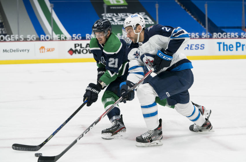 Feb 19, 2021; Vancouver, British Columbia, CAN; Winnipeg Jets defenseman Dylan DeMelo (2) checks Vancouver Canucks forward Loui Eriksson (21) in the first period at Rogers Arena. Mandatory Credit: Bob Frid-USA TODAY Sports