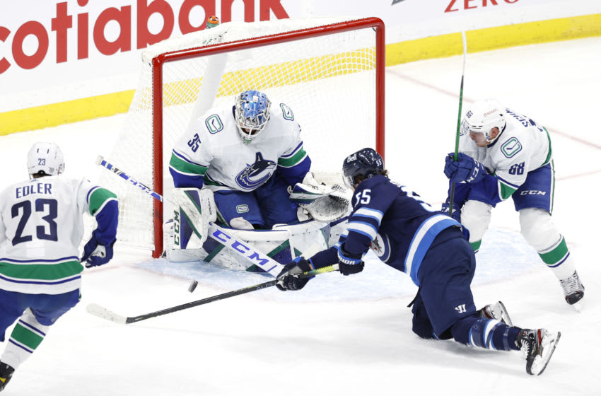 Mar 1, 2021; Winnipeg, Manitoba, CAN; Winnipeg Jets center Mark Scheifele (55) moves in for a shot on Vancouver Canucks goaltender Thatcher Demko (35) in the third period at Bell MTS Place. Mandatory Credit: James Carey Lauder-USA TODAY Sports