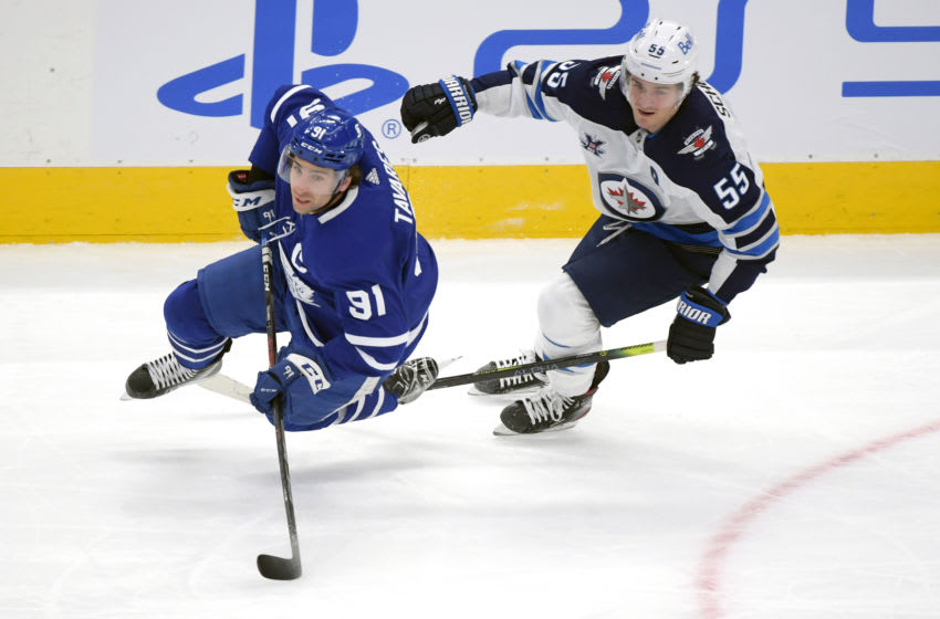 Mar 13, 2021; Toronto, Ontario, CAN; Winnipeg Jets forward Mark Scheifele (55) earns a minor penalty for tripping Toronto Maple Leafs forward John Tavares (91) in the first period at Scotiabank Arena. Mandatory Credit: Dan Hamilton-USA TODAY Sports